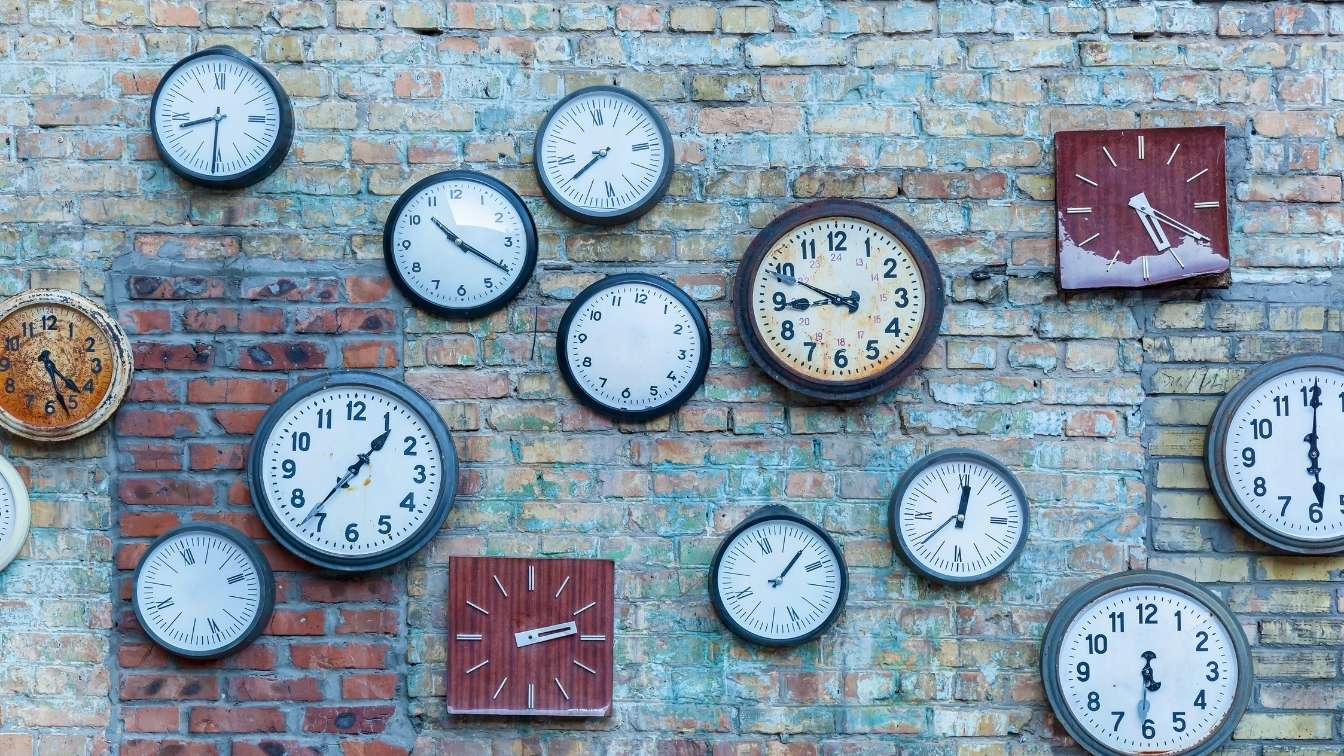 Different shapes and sizes of clocks on brick wall