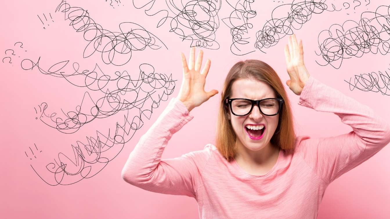 Girl in pink top surrounded by lines and squiggles withhands by head in frustration