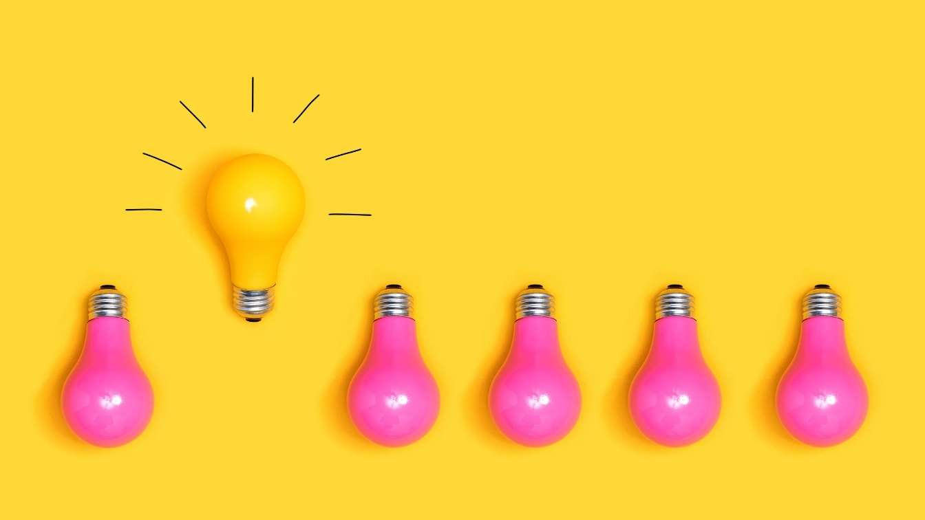 One yellow lightbulb standing out in a row of pink lightbulbs
