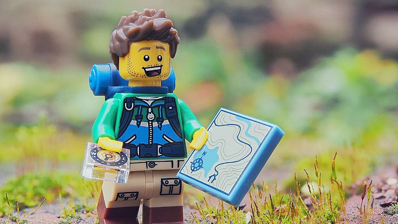 Lego man with compass and map starting on a journey
