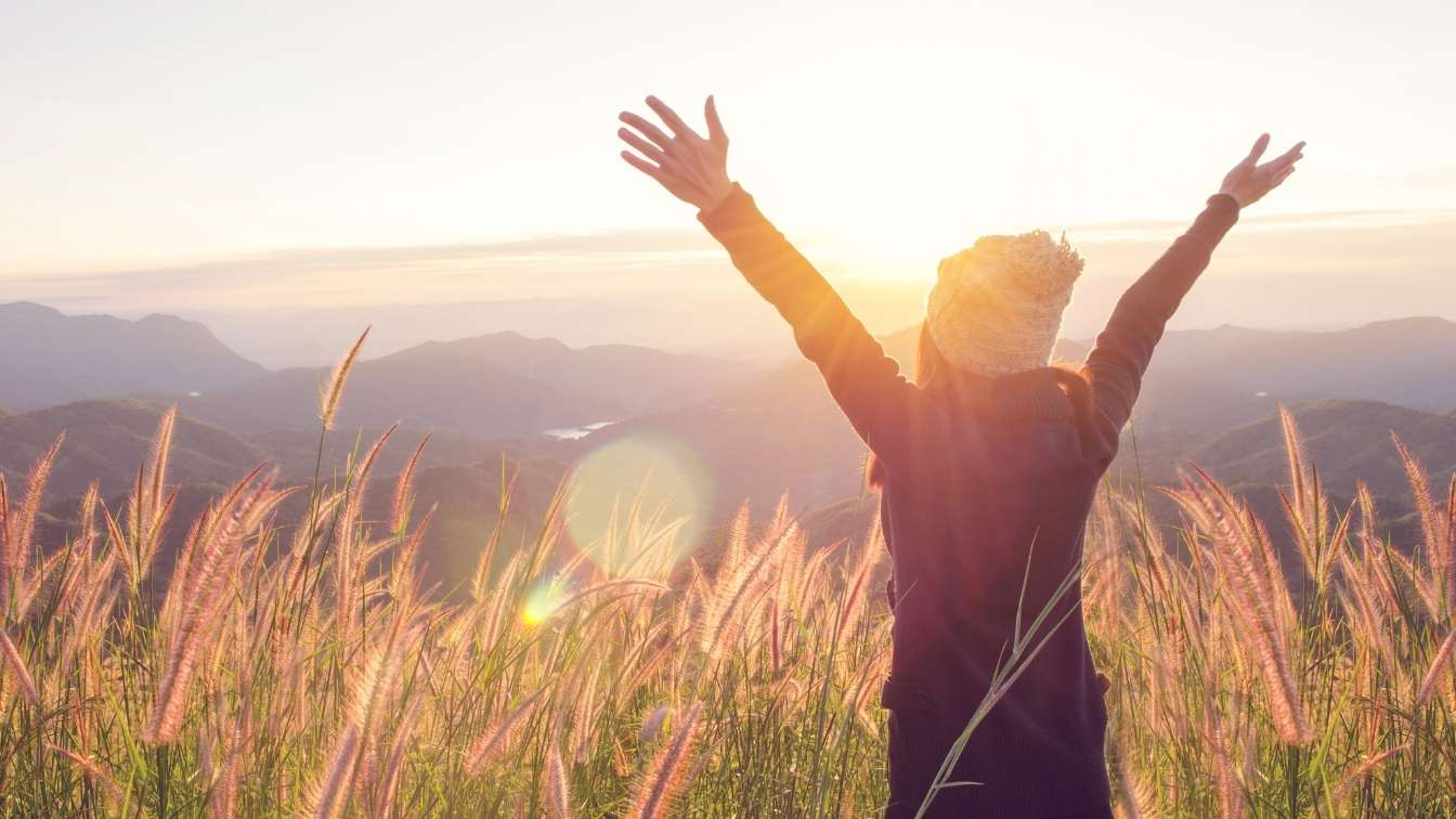 Woman in freedom pose in long grass at sunrise