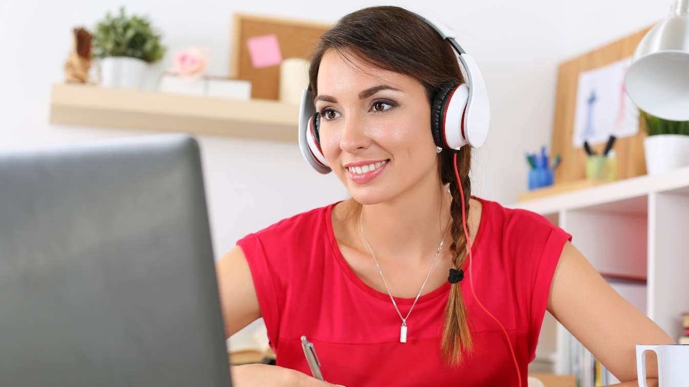 Woman with headphones and laptop taking online seminar